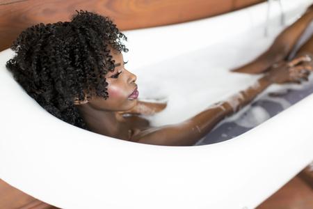 Bastante joven mujer de negro que tiene un baño de espuma en la habitación Foto de archivo - 60485994