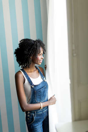 african american woman: African american woman posing by the wall