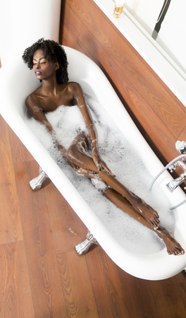 lying in bathtub: Pretty young black woman having a foam bath in the room