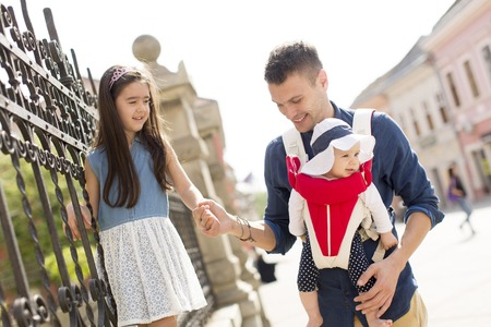 urban parenting: Young father with cute daughters on the street