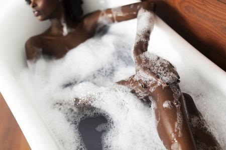 woman in bath: Pretty young black woman in the foam bath