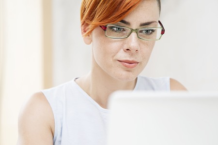 Young redhair woman working on a laptop