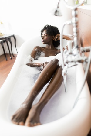 lying in bathtub: Pretty young black woman in the foam bath