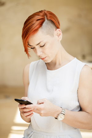 sidewalk talk: Red hair woman with side shaved hairstyle using a mobile phone