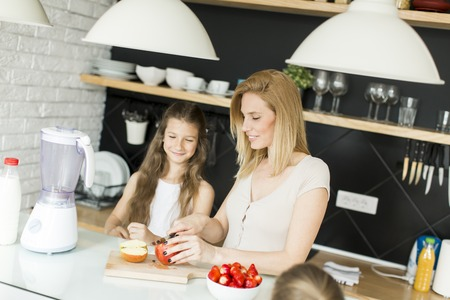 blending: Mother and daughter preparing and blending smoothie from fresh fruits in the modern kitchen