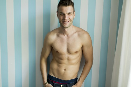 half naked: Half naked young man in front of the wall