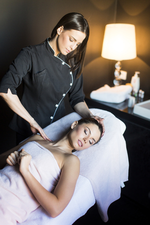 Pretty young woman having a massage in wellness center Stock Photo