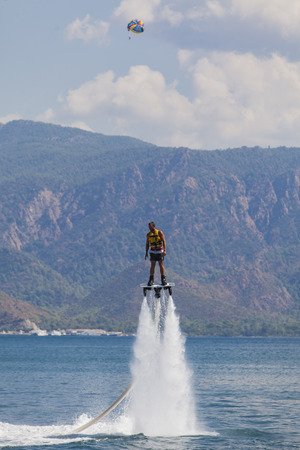 throttle: MARMARIS, TURKEY - SEPTEMBER 17, 2014: Unidentified man on flyboard at Marmaris, Turkey. Flyboard was invented in spring 2011 by a French watercraft rider, Franky Zapata.