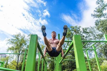 and the horizontal man: Young man doing pull ups on horizontal bar outdoors
