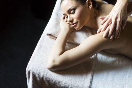 Pretty young woman having a massage in wellness center Reklamní fotografie