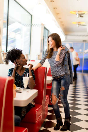 diner: Two young women socializing in the diner Stock Photo