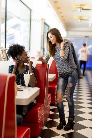 socializando: Dos mujeres jóvenes que socializan en el restaurante