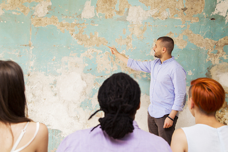 speaks: Young man speaks to other young people by grunge wall