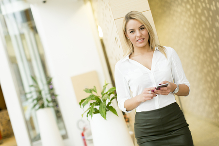 attractive  female: Pretty young blond woman using a mobile phone in the modern office
