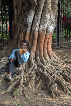 agglomeration: MUMBAI, INDIA - OCTOBER 9, 2015: Unidentified man reading a book on the street of Mumbai, India. With 12 million people, Mumbai is the most populous city in India and the 9th most populous agglomeration in the world.