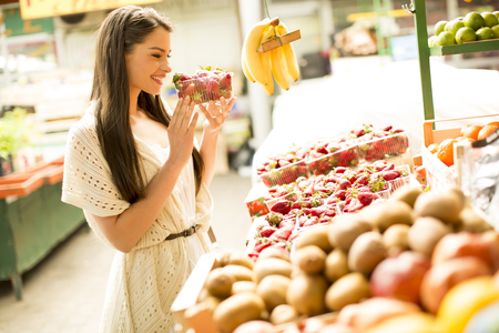 Young woman looking and buying fresh fruit at the market Stock Photo