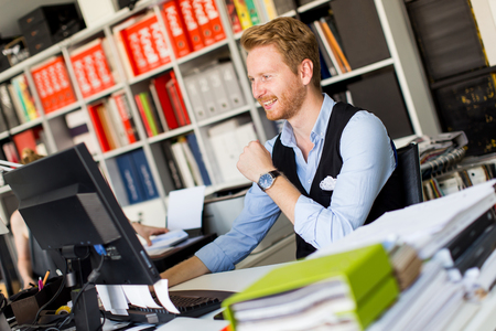 elite: Successful young businessman at desk in office