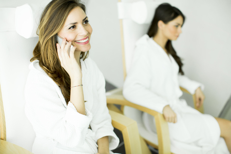 bathrobes: Woman with telephone and other woman in bathrobes relaxing in the spa Stock Photo