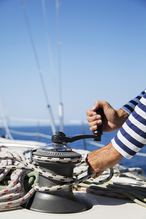 Young handsome sailor pulling rope on sailboat Stock Photo