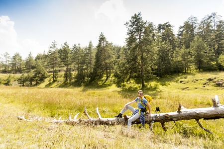 felled: Young hiker sitting on a felled tree and resting