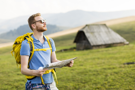 Young redhair man on mountain hiking holding a map Stock Photo