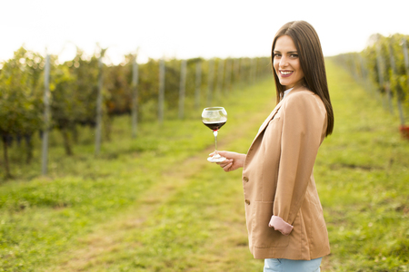 Vintner woman check red wine in a vineyard