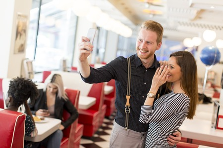 diner: Young couple taking selfie in the diner
