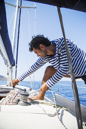 Young handsome sailor pulling rope on sailboat Stok Fotoğraf