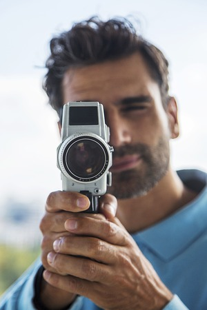 Handsome young man with old fashioned camera