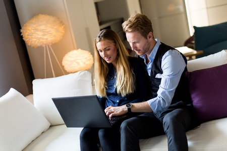 websurfing: Young couple sitting on the sofa and websurfing on internet