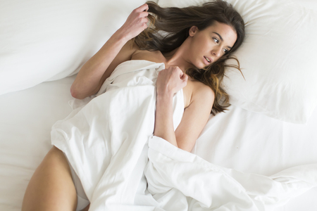Pretty young woman in the bed at home Stock Photo