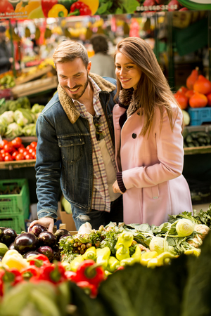 necessities: Young couple buying fruits and vegetables on a market