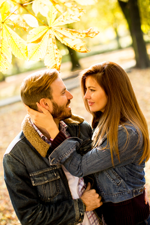 Loving couple exchanging tenderness in the autumn park