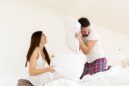 pillow fight: Couple having fun with a pillow fight in bed Stock Photo