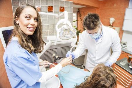 Paciente de la mujer joven que tiene tratamiento dental en el consultorio del dentista