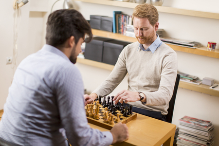 gamesmanship: Two young men playing chess in room