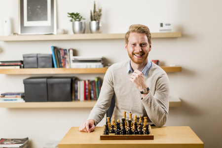 Portrait of a young man is playing a chess and looking at the camera. Reklamní fotografie