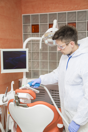 office cleanup: View at young man cleans dental clinic