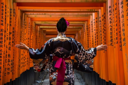KYOTO, JAPAN - OCTOBER 8, 2016: Unidentified woman at walkway in Fushimi Inari shrine in Kyoto, Japan. This popular shrine have 32,000 sub-shrines  throughout Japan Stock Photo