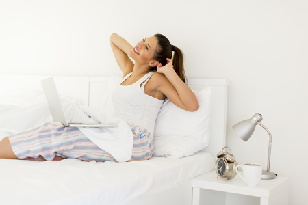 Young woman stretching in bed while her lap top standing on legs Stock Photo