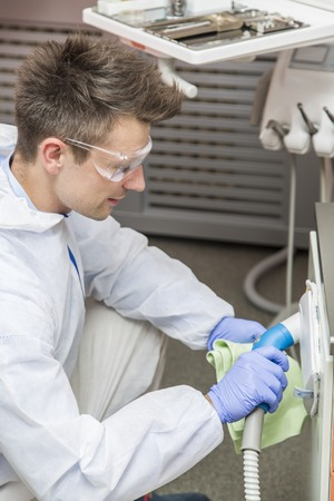 sterilize: View at young man cleans dental clinic