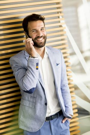 Handsome businessman in suit holding the phone in office