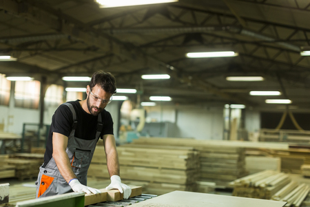 Young worker works in a factory for the production of furniture