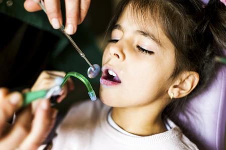Little girl getting dental treatment in dentist office