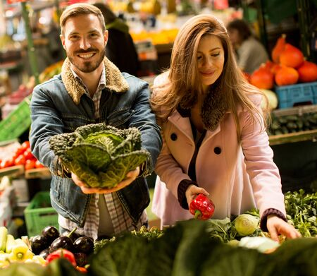 necessities: Young couple buying vegetables on a market