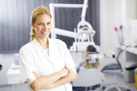 Atractiva mujer dentista que presenta en la oficina dental moderna