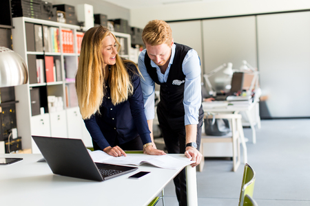 Young business couple analyzing business results Фото со стока