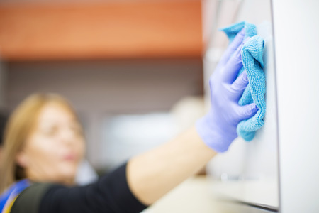 Woman at work, professional maid cleaning in dental office