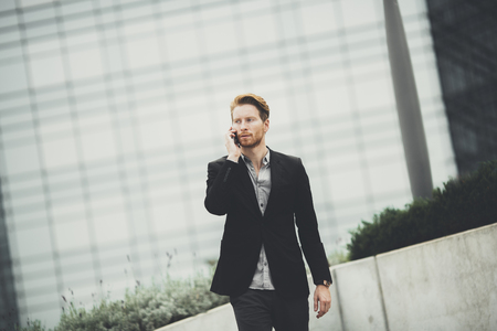 men talking: Young redhair businessman with mobile phone on the street Stock Photo
