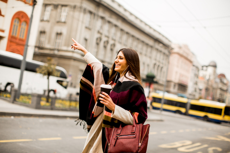 hailing: View at young woman hailing a taxi on the street in the city Stock Photo